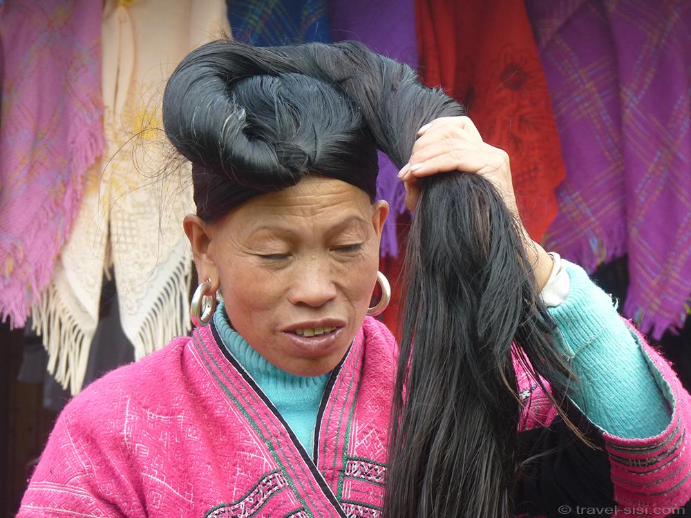 Zhuang Frau dreht Haare ein