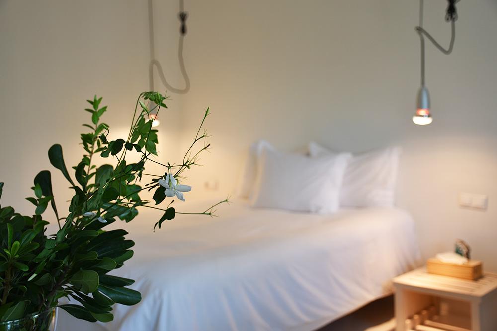 Ekies All Senses Resort Junior Suite Bett mit frischen Blumen