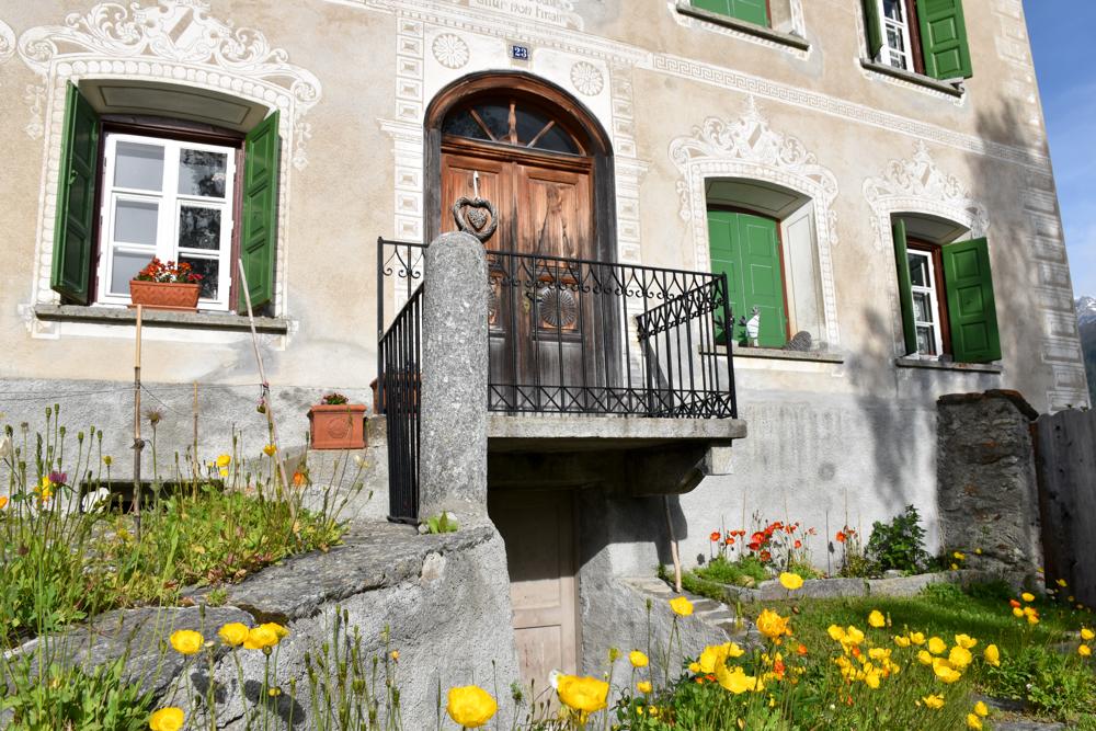Guarda und der Schellen-Ursli-Weg Engadiner Haus mit Blumen