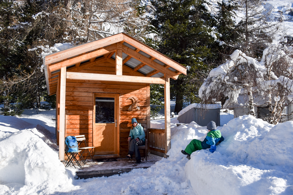 Winter Glamping Campingplatz Morteratsch Engadin Graubünden Schweiz Travel Sisi Esther Mattle mit Sohn vor dem Holzhaus