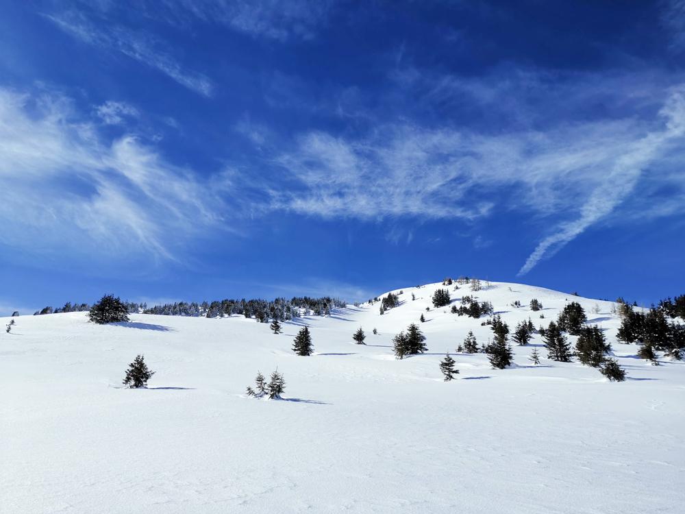 Winterwanderung Rundweg Feldis Viamala Graubünden Schweiz verschneiter Berg und blauer Himmel